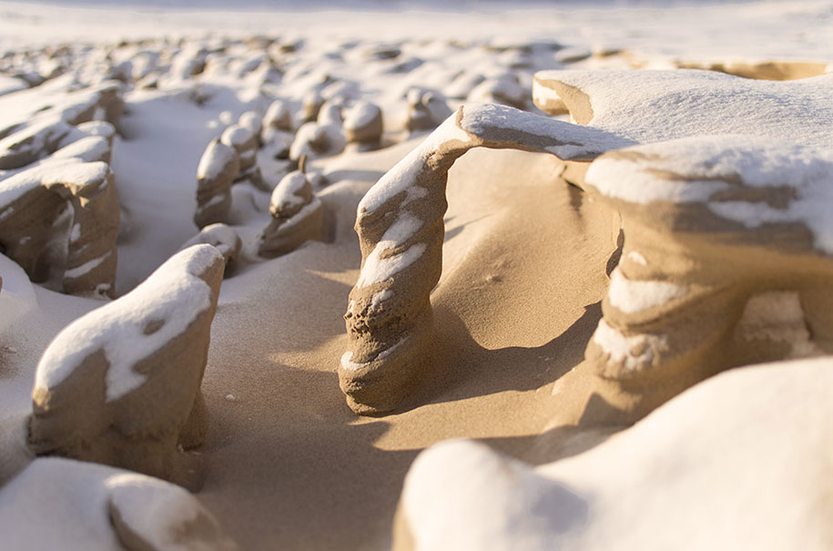 Frozen sand towers carved by strong winds on the shores of