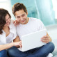 Tilt up of couple using laptop at home